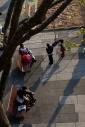 People sitting on benches, in the late afternoon sun, on the south bank, London