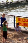 Children bury a man on the man-made beach on the south bank in London