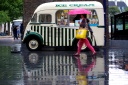 A woman with an umbrella hurries past an ice cream van