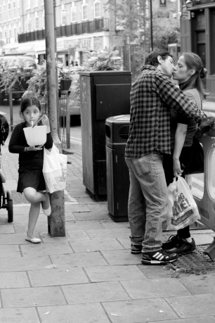 Couple kissing while a child waits