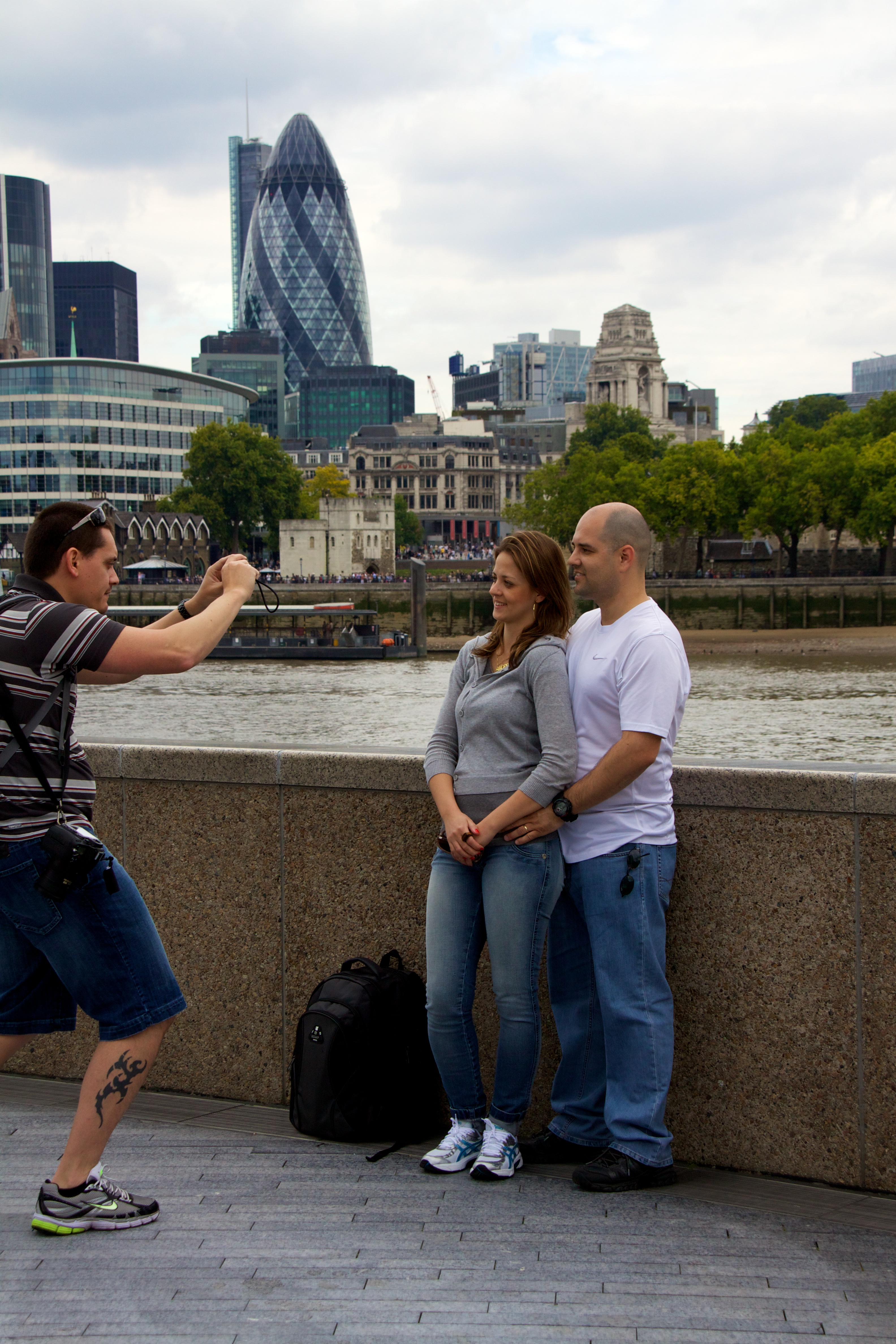 Man taking a photo of a couple on the South Bank in London with the Gherkin in the background