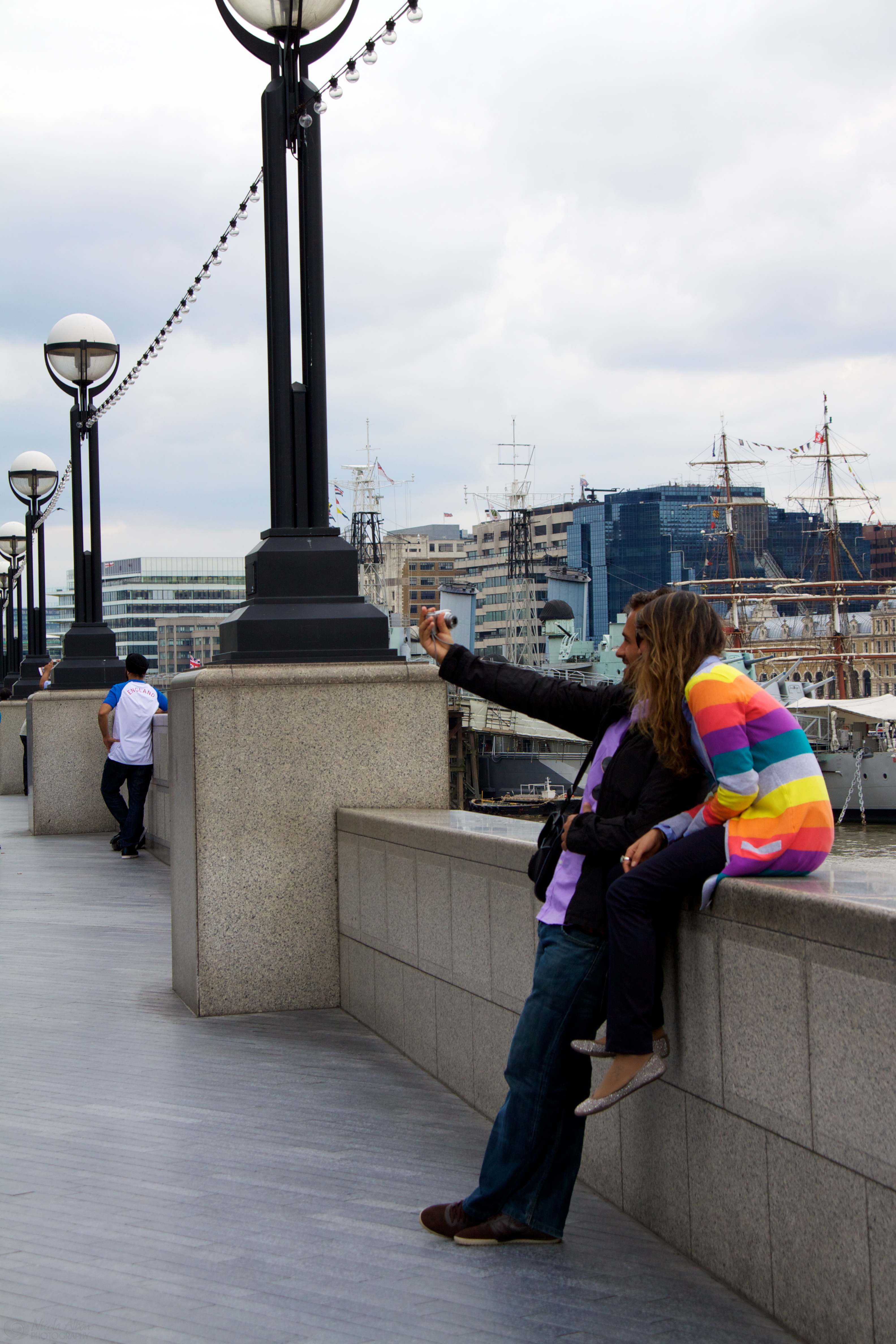 A couple taking their own photo outside City Hall in London