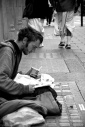 Homeless man reads a newspaper while begging in the street in London