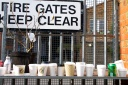 Row of cups on a shelf in front of a gate with keep clear sign