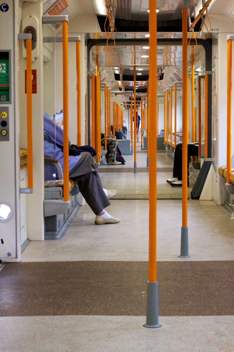 Orange posts and a few people's legs inside a London Overground train