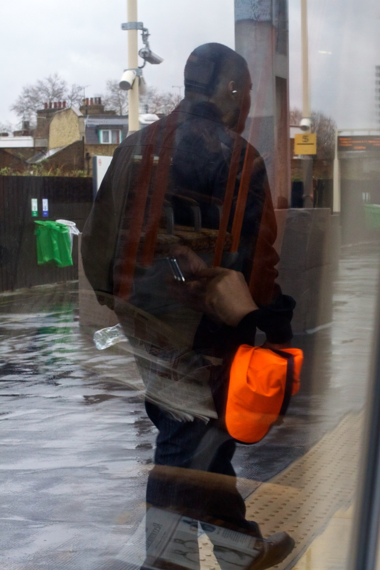 A man boards the London Overground, with reflections of the inside of the train in the window
