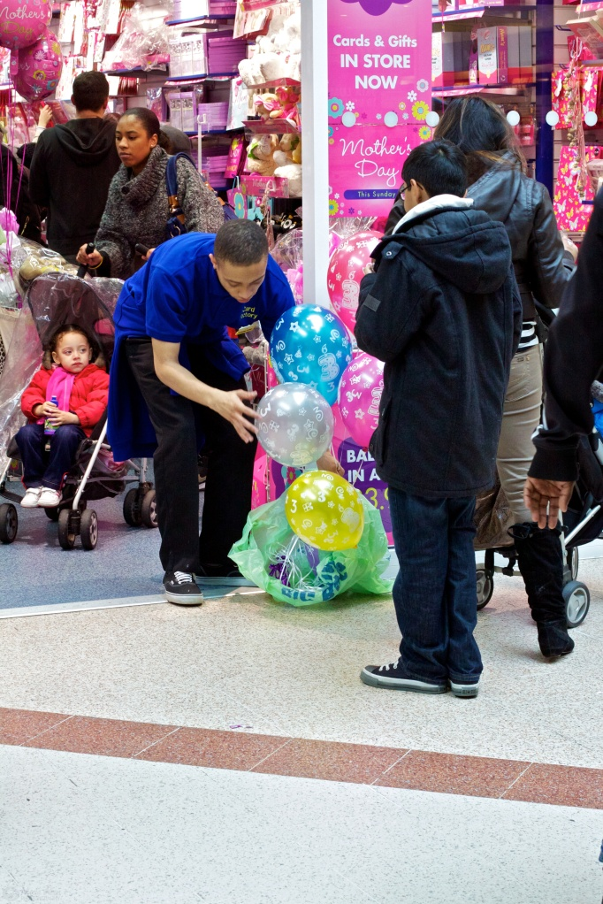 A sales assistant tries to stuff helium-filled balloons into a bag outside a card shop