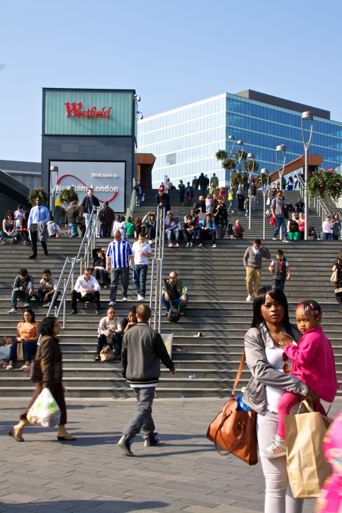 People sitting on the steps up to Westfield Stratford on a sunny day