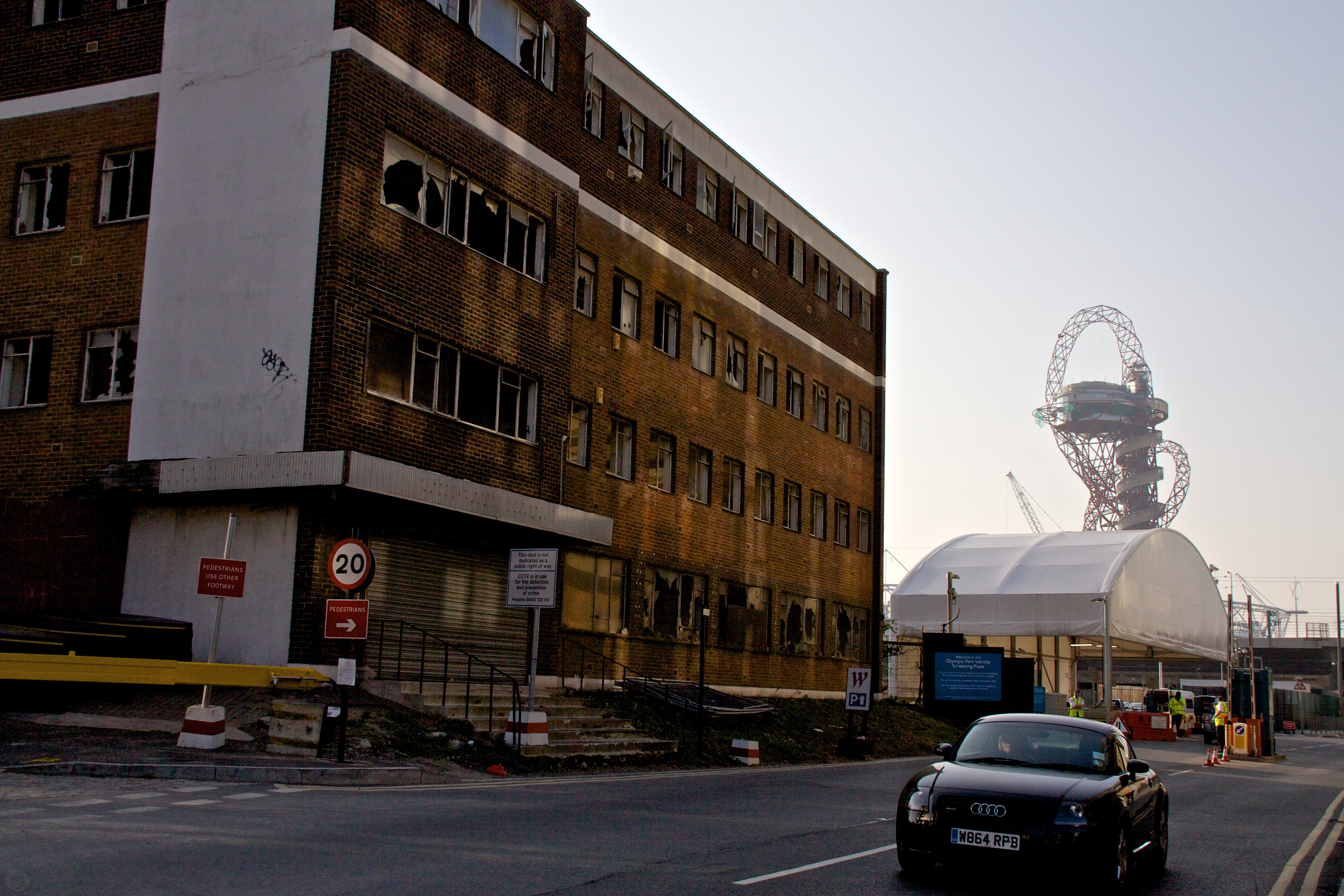 View of the entrance to the Olympic site with a derelict building