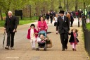 A girl wears a bowler hat as she walks with her family through Hyde Park