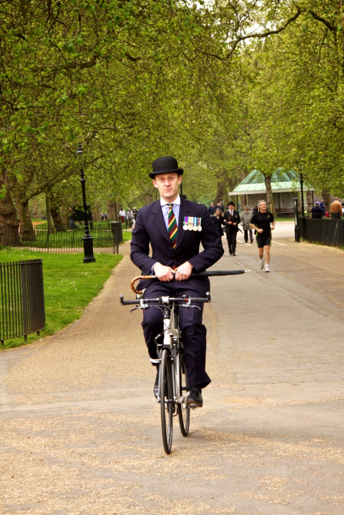 A man wearing a pin-stripe suit and bowler hat rides his bicycle through Hyde Park, London