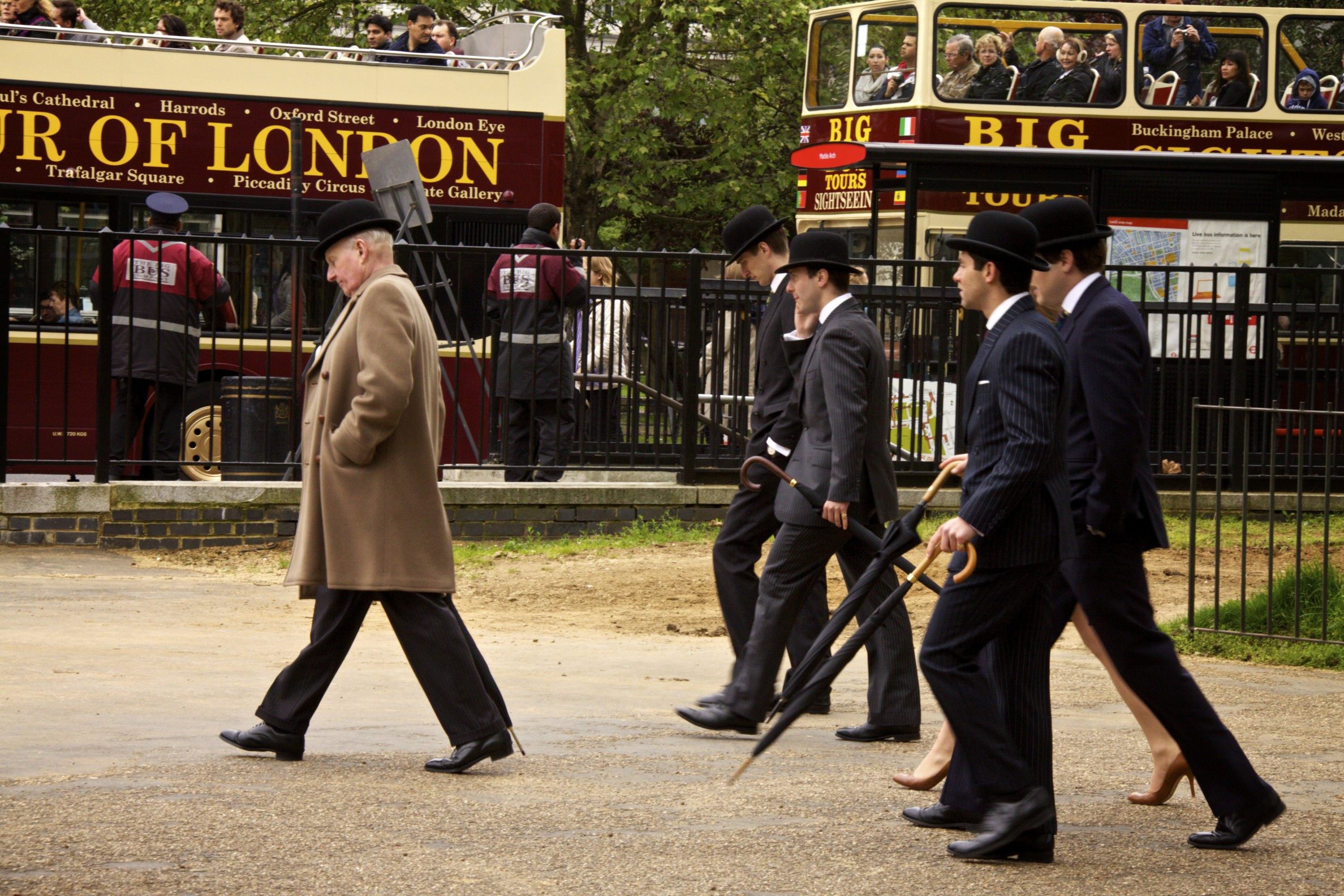 A group of men in pin stripe suits and bowler hats follow an older man in a crombie and bowler hat through Hyde Park in London