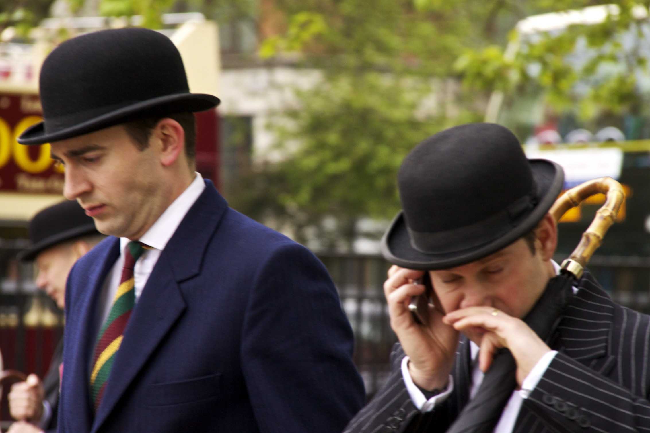 Two men in bowler hats, one sneezes while on his mobile phone