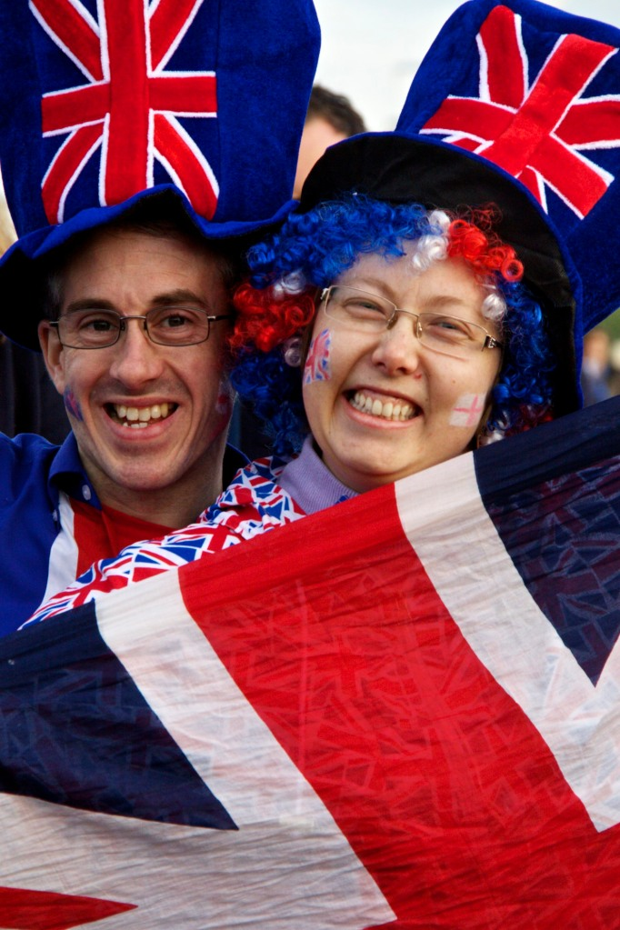 A couple in matching Union Jack/Flag hats and outfits smile and pose for the camera