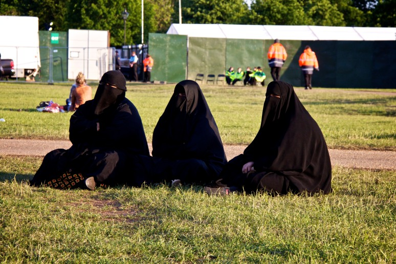 Three muslim women covered head to toe in black, sitting on the grass, watching the Diamond Jubilee concert on the big screen at Hyde Park
