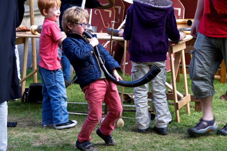 A boy blows a horn at an event at the British Museum