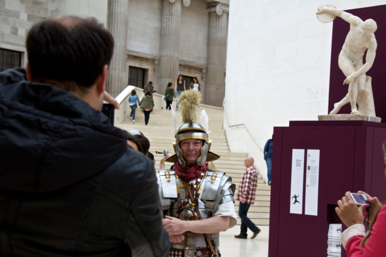 People taking photos of a man dressed as a Roman centurion or ancient Greek at British Museum