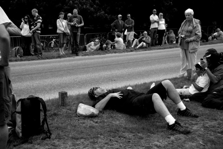 A man in cycling gear lies on the grass while a woman looks at him strangely