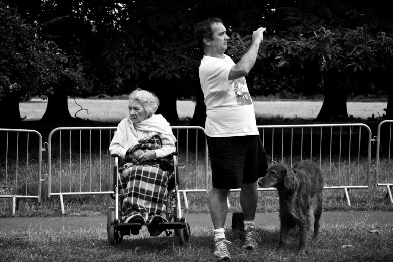 A woman in a wheelchair with a blanket over her legs and a man photographing something