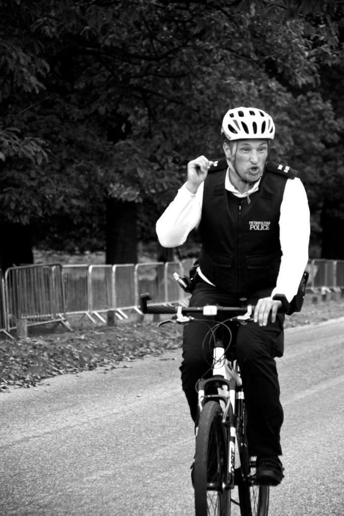 A cycling police officer makes a triumphant gesture to the crowd