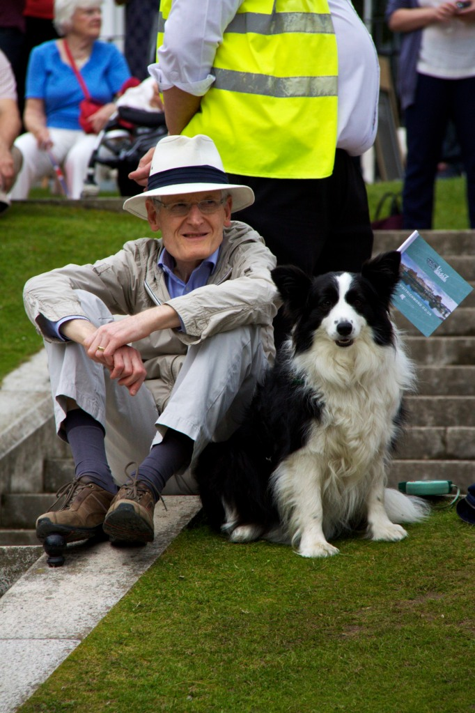 A man and a sheep dog sitting waiting for Olympic flame procession to arrive