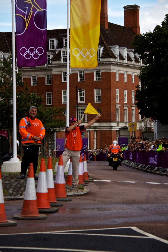 A steward holds a flag, waiting for the women's Olympic cycling road race to arrive