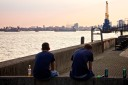 Two young men sit drinking cans of beer on a summer evening in North Woolwich, London, looking towards the Thames Barrier