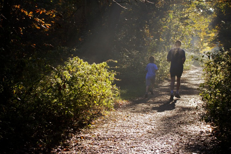 A man and a boy jogging through woods on a sunny autumn morning