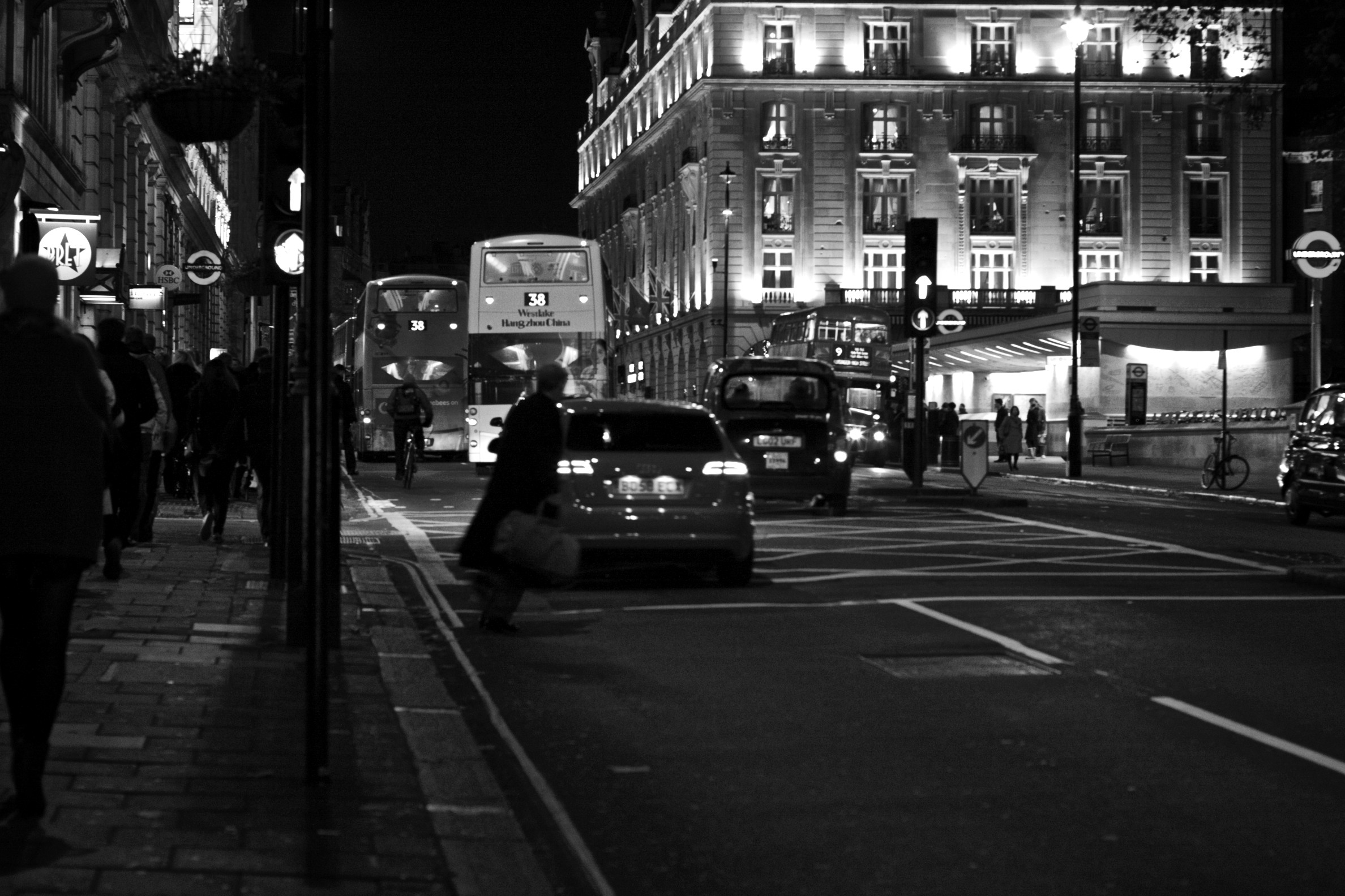 A Crossing On Piccadilly London At NightA Commuter In Hurry Leans Out Into The Road Night Black And White