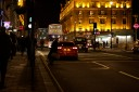 A commuter in a hurry leans out into the road at a crossing on Piccadilly, London, at night