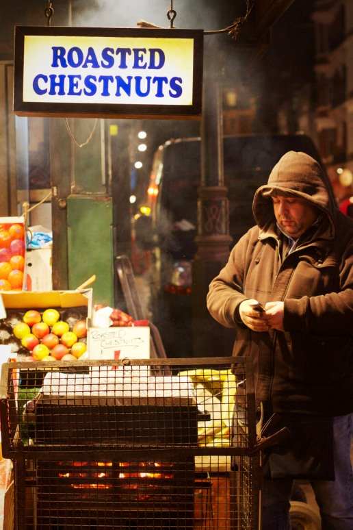 A man selling roasted chestnuts at market stall