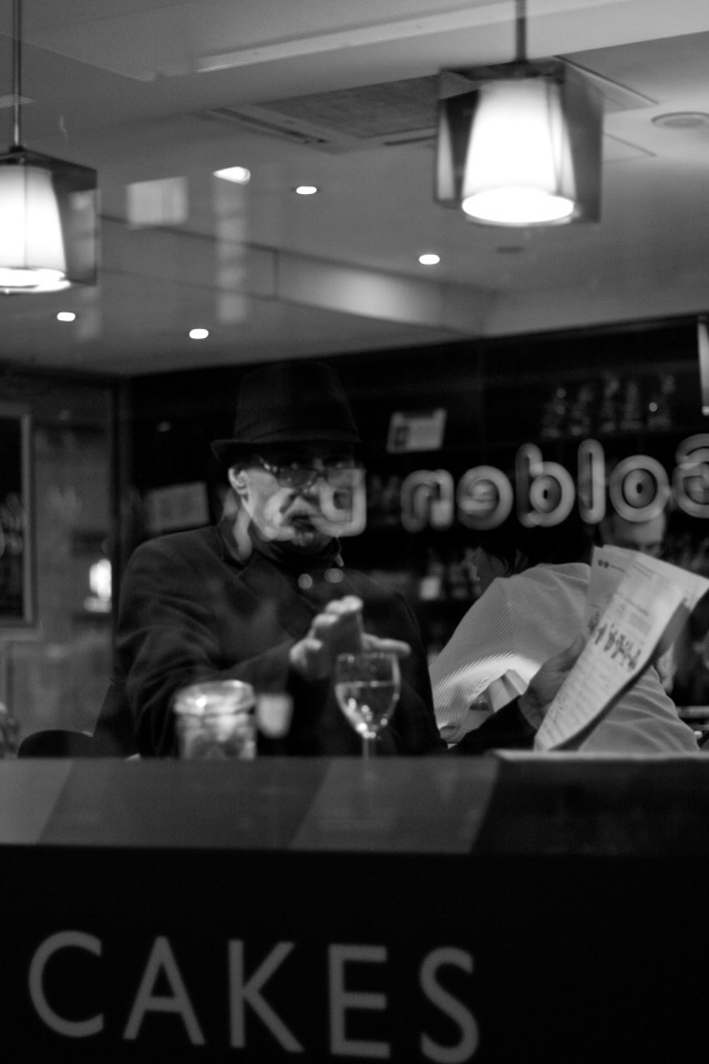 Man reading a newspaper looks up at photographer