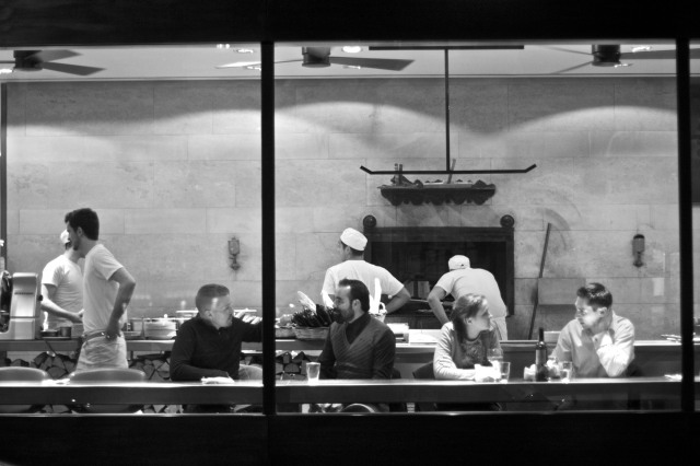 Looking into a pizza restaurant at night, with four people seated facing out towards the street and chefs at work