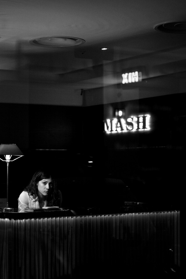 Woman on a reception desk looks out through a glass door at the photographer