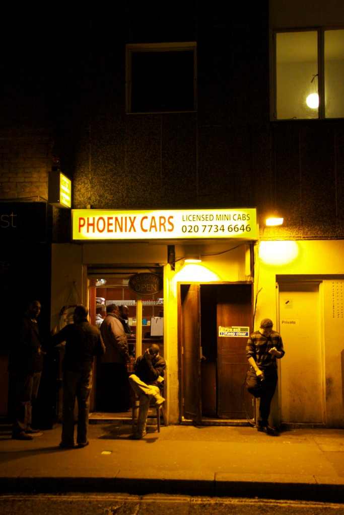 Cab drivers outside a minicab office in Soho, London, at night