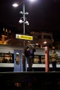 Man stands under a light reading a newspaper on the platform at Charing Cross Station, London