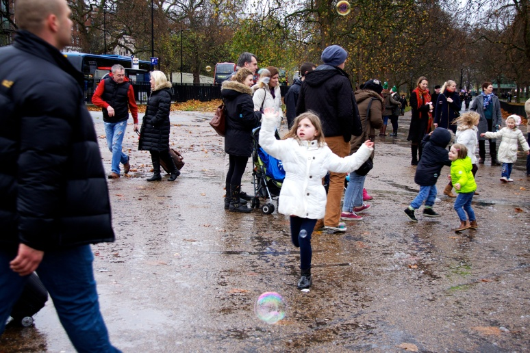 Girl chasing bubbles in Hyde Park, London