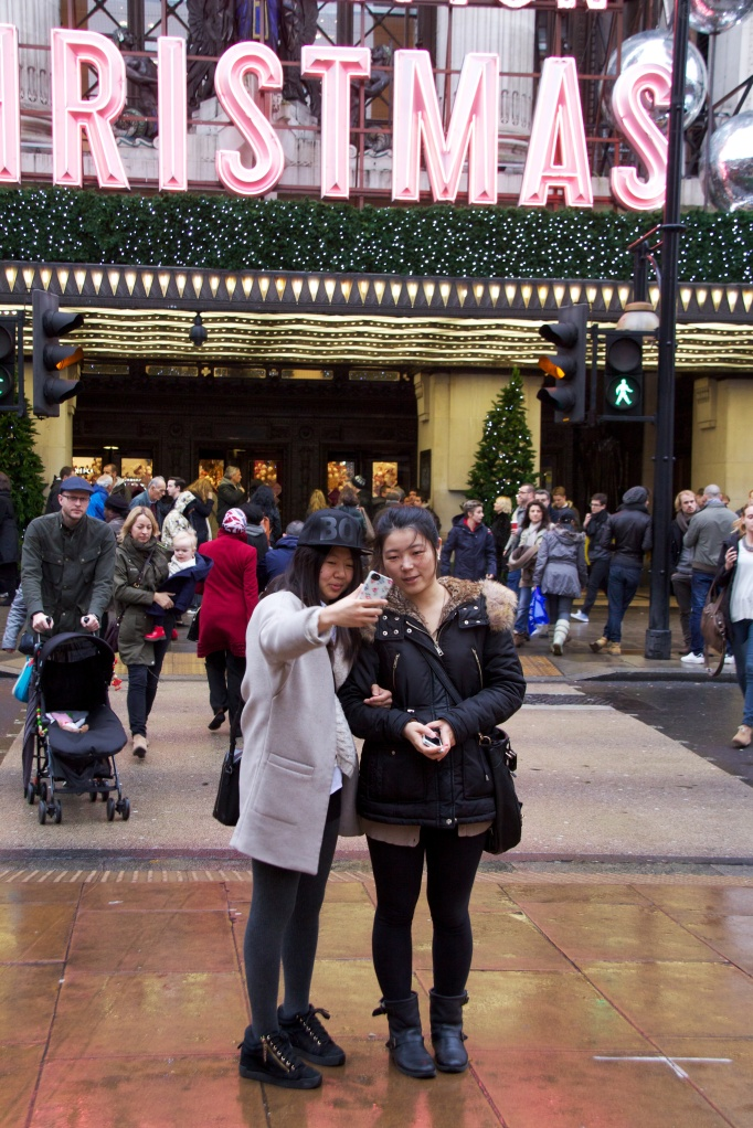 Two girls take a selfie outside Selfridges on Oxford Street, London, at Christmas
