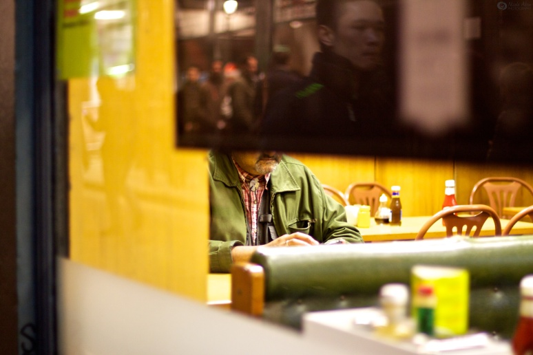 Man sitting in cafe is obscured by a screen which has a reflection of another man outside the cafe on it