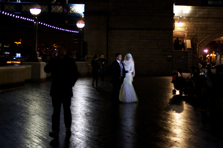 A bridge and groom pose for photos by Tower Bridge and are captured in the light of a flash