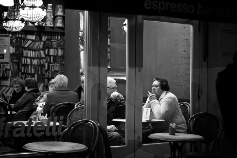 A woman spotlighted through a cafe window
