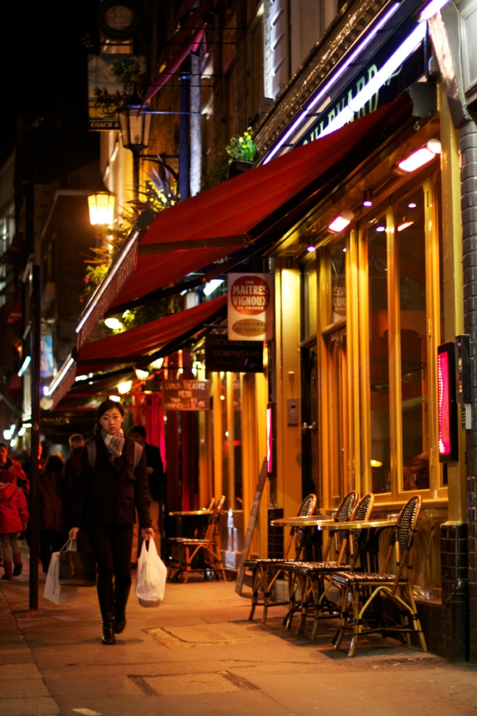 Woman carrying shopping bags, walking past cafe at night