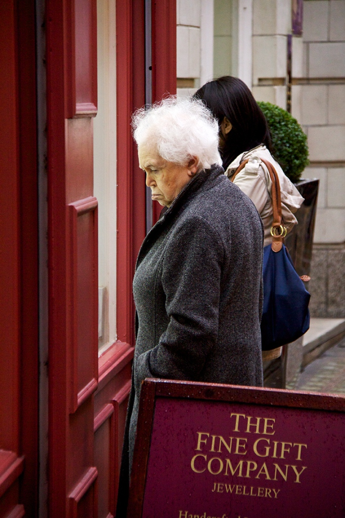 Elderly woman looking in shop window