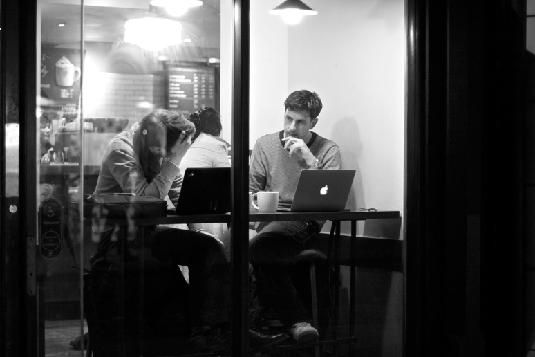 Two young men in a cafe window with their laptops