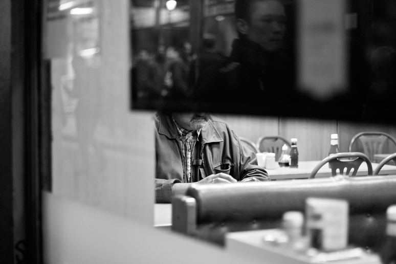 Looking through a window at a man in a cafe, obscured by a screen on which there is a reflection of another man walking past