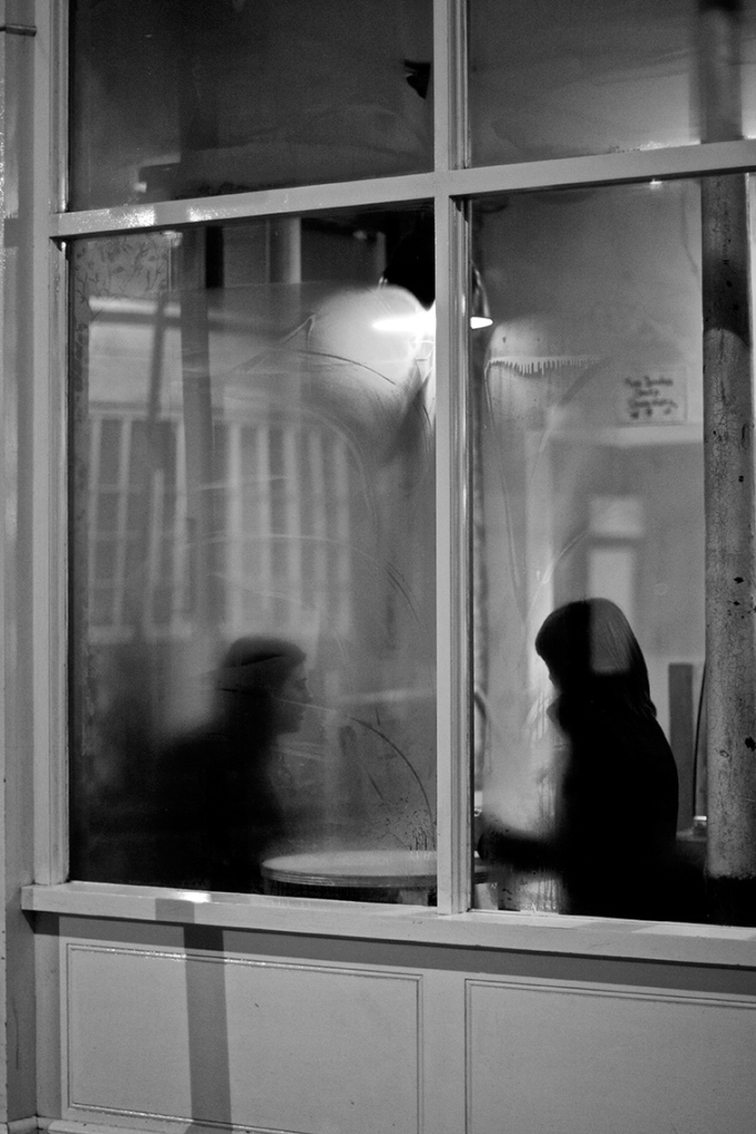 Condensation on a cafe window blurs the outlines of two women