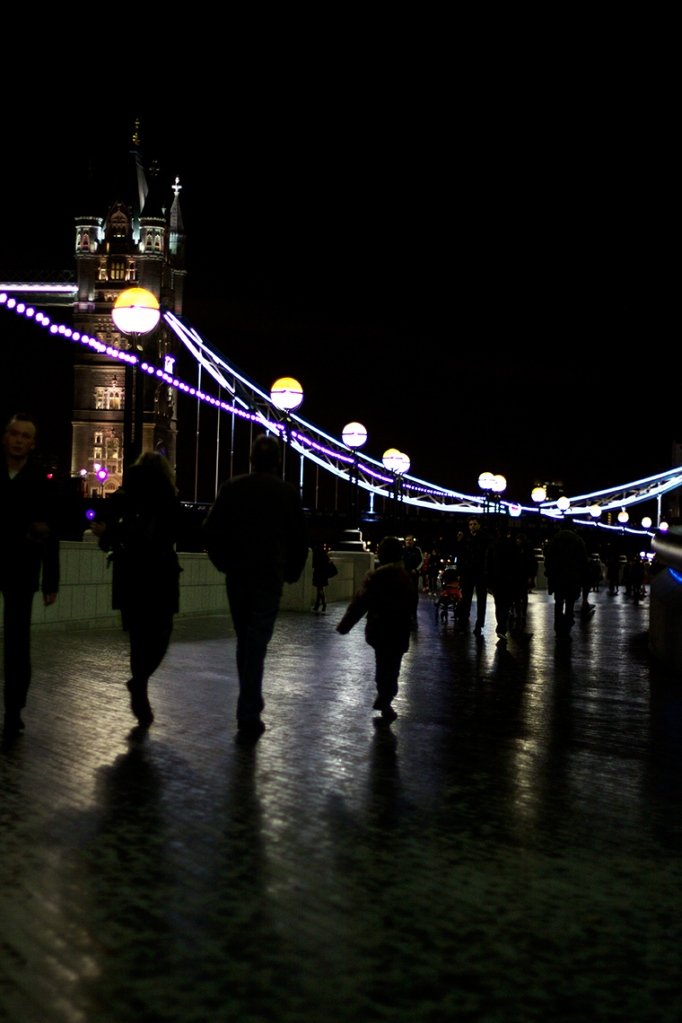 Colour photograph of people walking along a wet path by the River Thames, their shadows visible in the wet pavement with Tower Bridge in the backgound