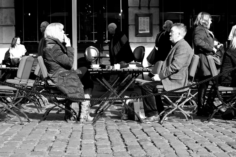 A couple having coffee at a cafe in London, the woman is smoking