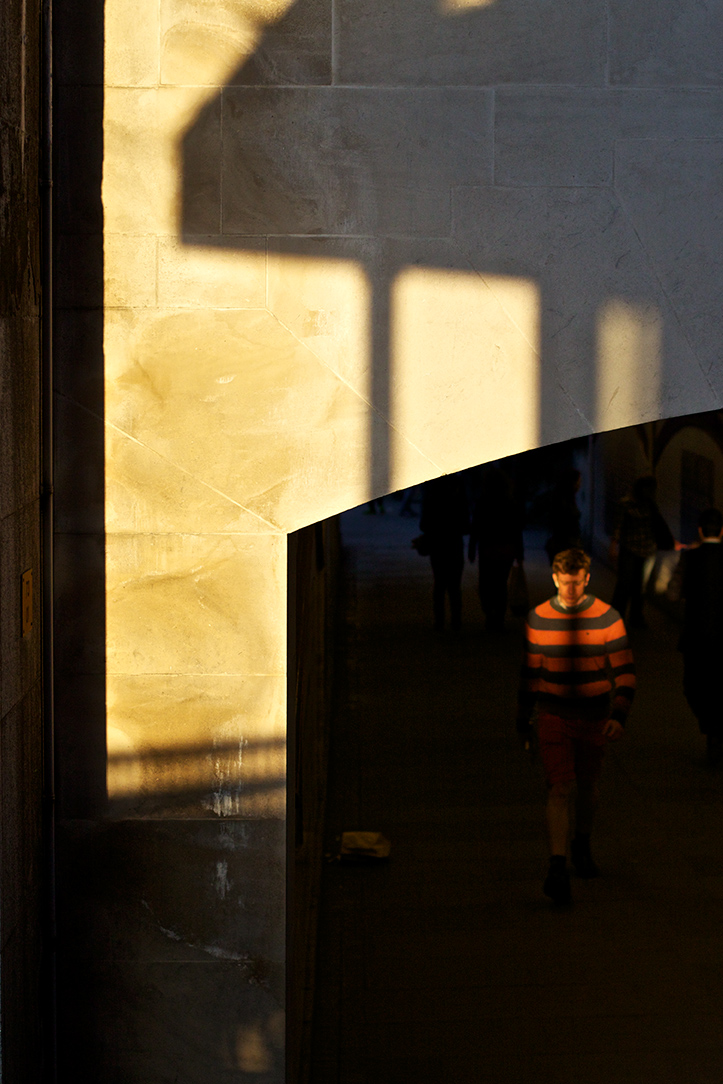 A man in a stripey jumper walks into a shaft of sunlight