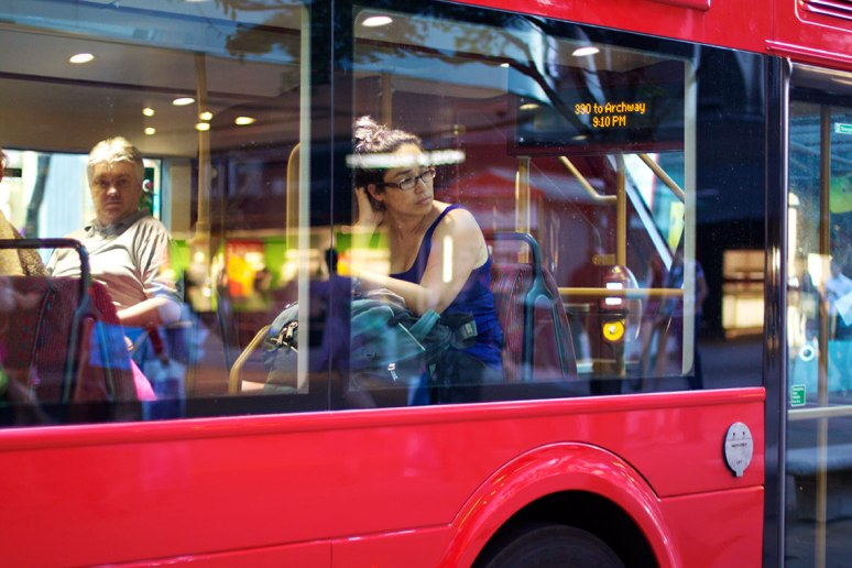 Young woman looking out of a window on a bus